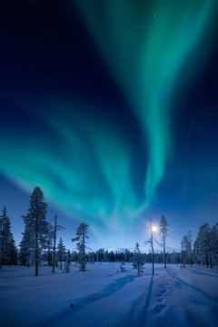 Moon and Northern Lights above Pallas fells with fresh snow at winter night in Pallas-Yllästunturi national park in Muonio, Finland