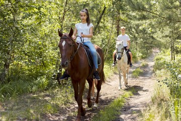 Group of teenagers on horseback riding in summer park
