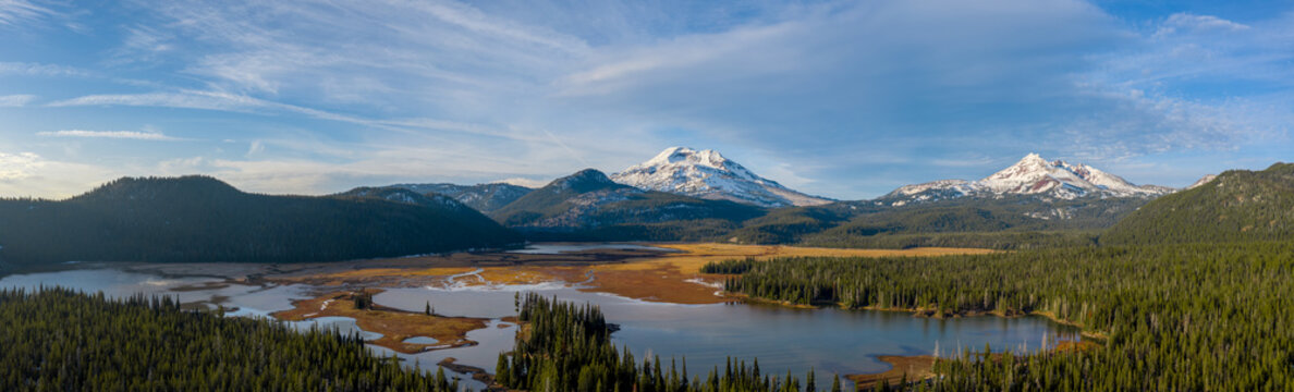 Aerial panorama view of picturesque northwest natural landscape with beautiful snowcapped mountains in distance past tranquil lake