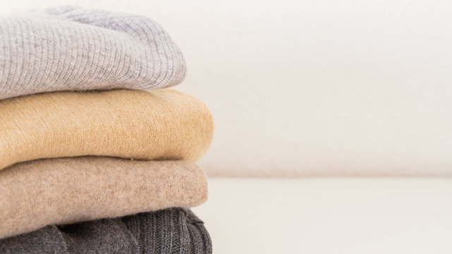 Stack of cozy knitted sweaters in beige grey colour on white background with copy space.  Warm comfortable clothes for Autumn Winter season.