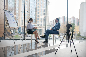 Investor giving the interview to famous journalist sitting near window