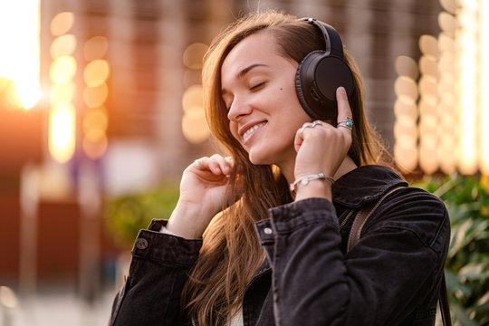 Happy joyful stylish casual fashionable hipster student woman teenager enjoys listening music using black wireless headphones while walking around the city. Music lover