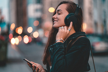 Young happy stylish trendy casual hipster woman teenager listening to music on a black wireless headphone while walking around the city. Music lover enjoying music Fotobehang