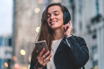 Young happy stylish trendy casual hipster woman changes songs and tracks on smartphone during listening to music on a wireless headphone while walking around the city. Music lover enjoying music
