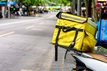 A yellow food delivery pouch on the back of a motorcycle in downtown Melbourne