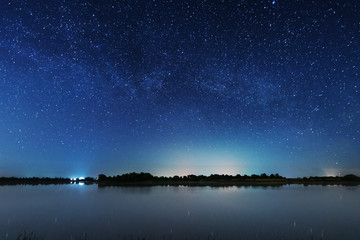 A magical starry night on the river bank with a large tree and a milky way in the sky and falling stars in the summer. Fotomurales