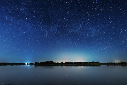 A magical starry night on the river bank with a large tree and a milky way in the sky and falling stars in the summer.