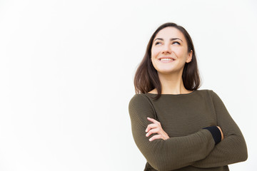Happy confident beautiful woman with arms crossed looking up at copy space, and smiling. Young woman in casual standing isolated over white background. Promotion concept
