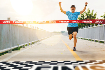 Excited man runner crossing the 2020 finish line of marathon. 2020 success concept.