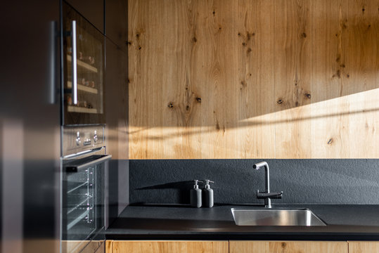 Modern minimalistic kitchen with black and wooden surfaces and household appliances on a sunlight