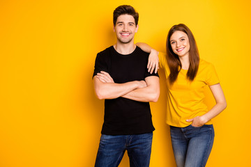 Photo of cheerful nice cute pretty beautiful couple of two people standing confidently in black t-shirt jeans denim arms crossed hand in pocket smile toothily isolated vibrant shiny color background