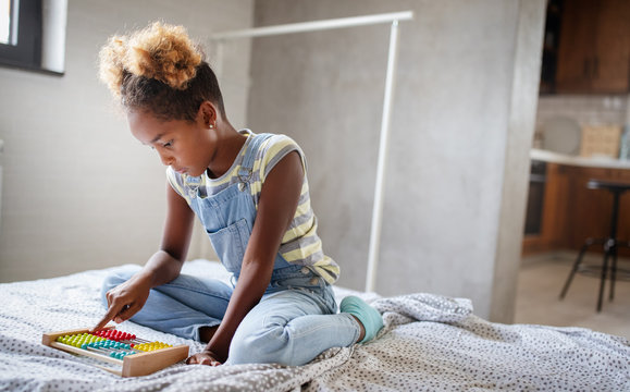 Happy african american kid girl learn to count at home with abacus