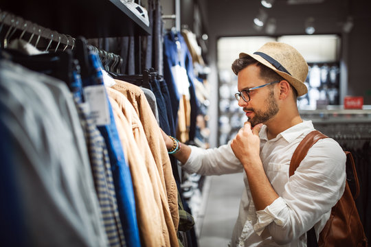 Handsome man shopping for new clothes in store