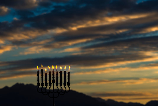 Light of candles are traditional symbol for Hebrew Holidays of Hanukkah. Blurred background with dawn sky, selective focus on candles