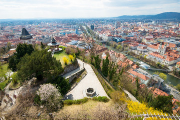 View at Graz City from Schlossberg hill, City rooftops, Mur river and city center, clock tower.