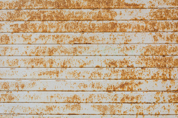 Background grey weathered metal shutters with orange rust