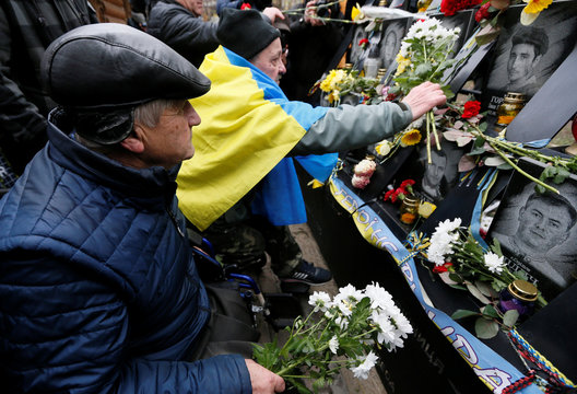 """People attend a commemoration ceremony at a monument to the so-called """"Heavenly Hundred"""" to mark the sixth anniversary of the start of the anti-government uprising in Kiev"""