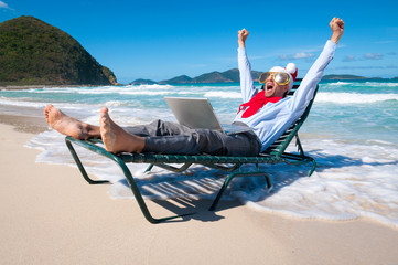 Excited Santa businessman celebrating Christmas shopping success with his laptop on a tropical beach