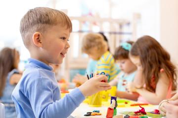 Preschool child on lesson in classroom. Kids group hands crafting in kindergarten
