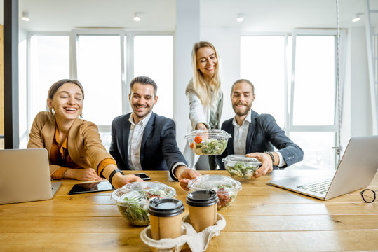 Portrait of a group of office workers taking business lunches in the office. Concept of healthy takeaway food on the work