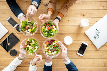 Office workers during a business lunch with healthy salads and coffee cups, view from above on the wooden table
