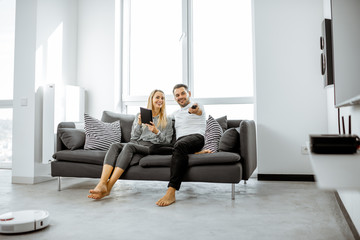 Young couple relaxing on the comfortable couch, watching television in the bright living room of the modern apartment Fototapete