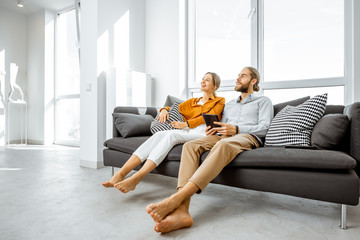 Happy young couple sitting together on the couch in the bright living room of the modern apartment, enjoying their new home