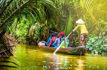 Wall Mural - Tourist enjoying Mekong delta cruise with canoe on Vietnam