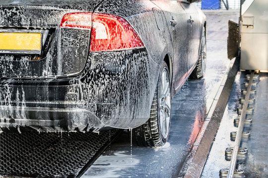 Auto carwash. Part of a car in white soapy foam. Automatic washing of a black car.