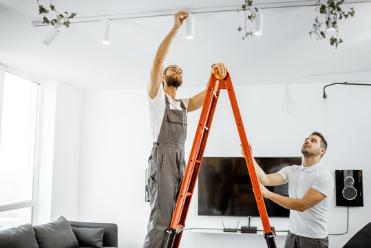 Two repairmen or professional electricians installing light spots, standing on the ladder in the living room of the modern apartment