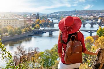 Touristin mit Hut genießt die Aussicht auf die Karlsbrücke und die Altstadt von Prag, Tschechiche Republik, an einem sonnigen Herbsttag