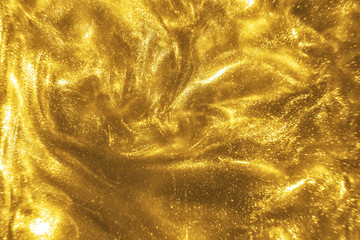 Abstract elegant, detailed gold glitter particles flow with shallow depth of field underwater....