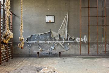 Ancienne salle  de gymnastique vide avec un banc et un ballon de football