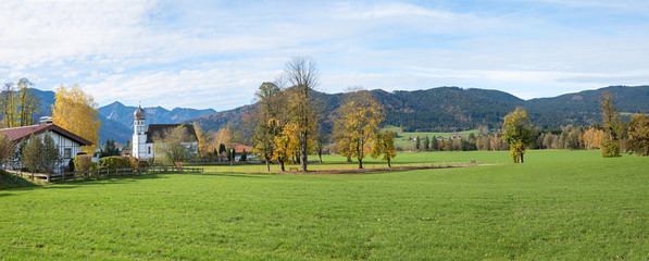 rural landscape with village church Fischbachau and autumnal trees, tourist resort bavaria