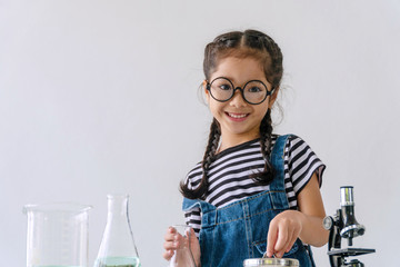 Little 6s cute girl smiling with microscope, laboratory bottle and water experiment study...