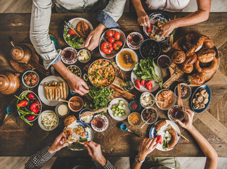 Turkish breakfast. Flat-lay of Turkish family eating traditional pastries, vegetables, greens, cheeses, fried eggs, jams and tea in copper pot and tulip glasses over rustic wooden background, top view Wall mural