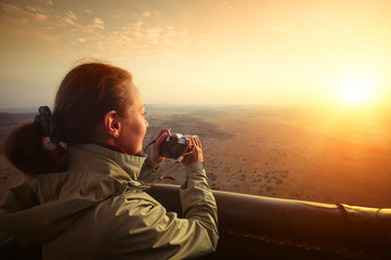 Fototapete - woman travels with camera flies in balloon over African savannah and watches sunrise