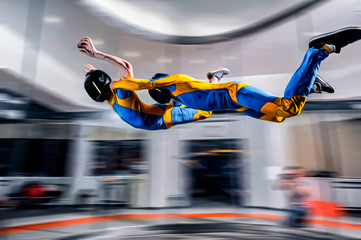 Flight. Peoples fly in wind tunnel. Indoor skydiving. Swim in wind tunnel. New sport in flight technology.