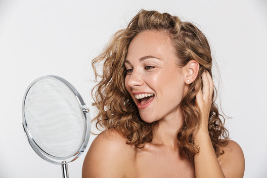 Image of excited half-naked woman smiling and looking at mirror
