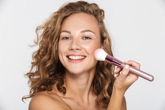 Image of beautiful half-naked woman smiling and using makeup brush