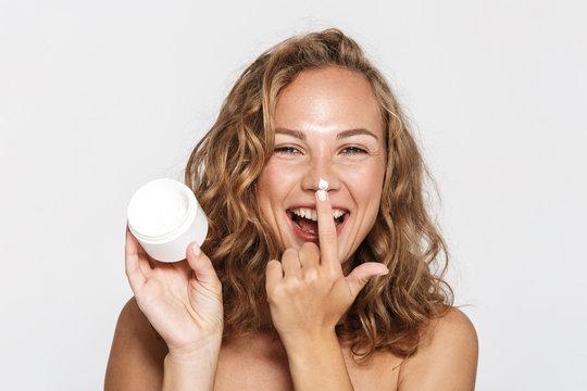 Image of cheerful half-naked woman making fun with facial cream