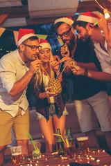 People drinking pineapple cocktail at New Year party