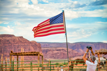 Male photographer taking pictures of american flag in the national park
