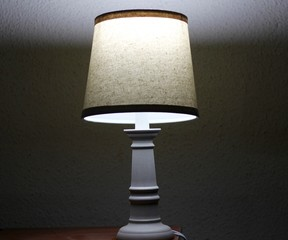 A lamp on the table in the room of the house.