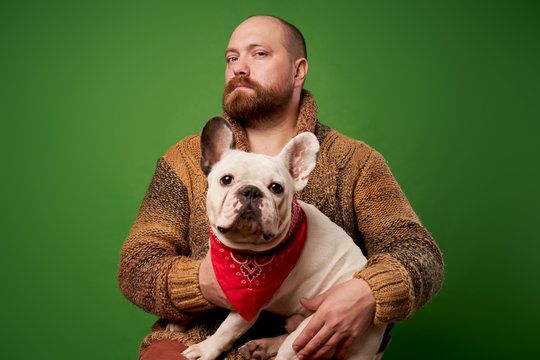 Male looking to side with french bulldog in his arms