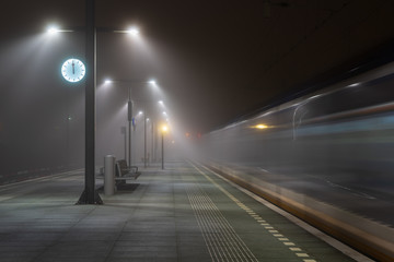 Train passing an empty platform at a railroad station during a foggy evening. Groningen, Holland. Fotomurales