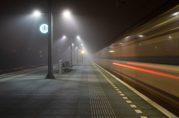 Train passing an empty platform at a railroad station during a foggy evening. Groningen, Holland.