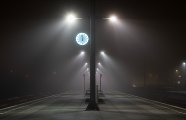 Illuminated, empty platform at a railroad station during a foggy night in autumn. Fotomurales