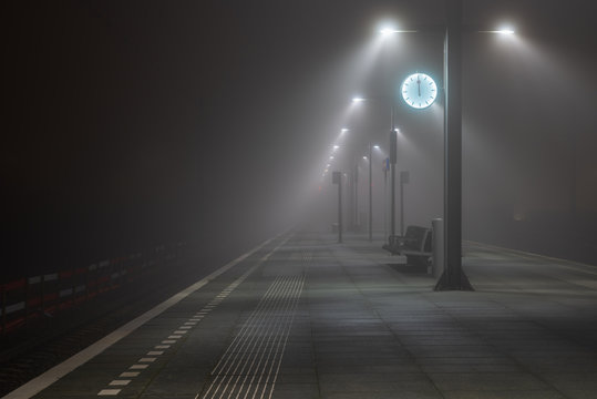Illuminated, empty platform at a railroad station during a foggy night in autumn.