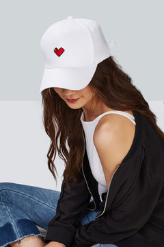 Cropped upward shot of a dark-haired girl, wearing white baseball cap with heart print, white tank top and black jacket. The cap peak is closing upper part of a face.